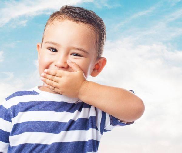 Мальчик закрывает рот рукой